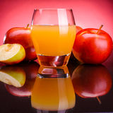 Glass of apple juice with apples. On a red background Royalty Free Stock Photos