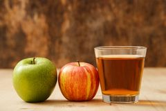 Glass of apple juice. With apples on the table Royalty Free Stock Images