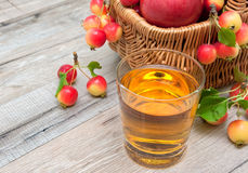 Glass of apple juice and a basket of apples Royalty Free Stock Photos