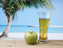 Glass of apple juice on a beach. Table Royalty Free Stock Image