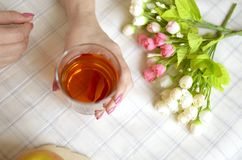 A glass of apple juice in female hands. Roses on a table Royalty Free Stock Image