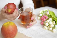 A glass of apple juice in female hands. Roses on a table Royalty Free Stock Photo