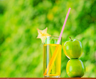 Glass of apple juice in a garden Stock Image
