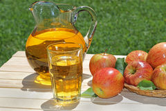 Glass of Apple Juice. Apple juice in a glasswith a pitcher and apples on a wood table Royalty Free Stock Photo