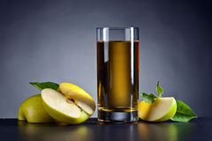 Glass of apple juice. Green apples and a glass of apple juice on a black ceramic table Royalty Free Stock Images
