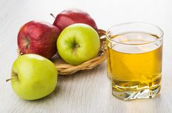 Glass of apple juice, green and red apples in basket Stock Photos