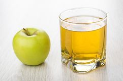 Glass of apple juice and green apple on table. Glass of apple juice and green apple on wooden table Royalty Free Stock Photography