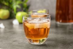 Glass of apple juice with ice cubes. On table Royalty Free Stock Images
