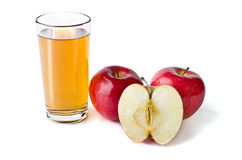 Glass of apple juice and red apples lying next  over whi Royalty Free Stock Images