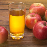 Glass of apple juice and red apples on wood Stock Photos
