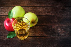 Glass of apple juice with red and green apples on wooden background Royalty Free Stock Photo