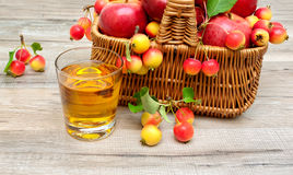 Glass of apple juice and ripe apples in a basket Royalty Free Stock Photo
