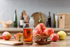 Glass of apple juice and ripe pink apples on a kitchen table Royalty Free Stock Photography