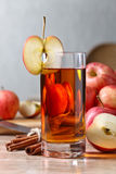 Glass of apple juice and ripe pink apples on a kitchen table Stock Photography