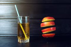 Glass of apple juice with sliced apple hanging in air Royalty Free Stock Photo