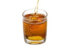 Glass of apple juice. In a transparent glass apple juice isolated on a white background is poured Stock Images