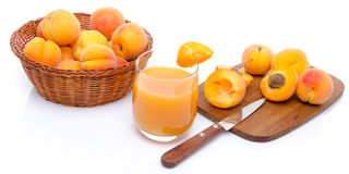 Glass of apricot juice with a basket of apricots and sliced apri Royalty Free Stock Photos