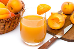Glass of apricot juice with a basket of apricots and sliced apri Stock Photos