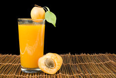 Glass apricot juice and fruits black . Royalty Free Stock Image