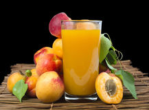 Glass apricot juice and fruits black isolated. Royalty Free Stock Image