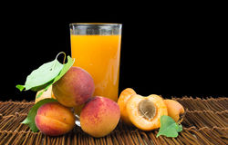 Glass apricot juice and fruits black isolated. Royalty Free Stock Photography