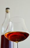 Glass of Armagnac. Close up of a glass of Armagnac with a bottle in background Royalty Free Stock Photography