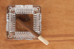 Glass ashtray with cigar stands on a wooden surface Royalty Free Stock Photo