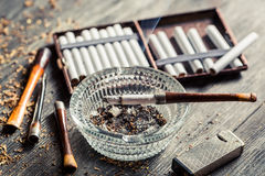 Glass ashtray with thin wooden pipes, cigarettes and lighter aro Stock Photo