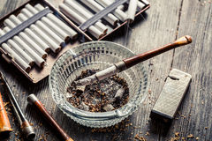 Glass ashtray with thin wooden pipes, cigarettes and lighter aro Royalty Free Stock Image