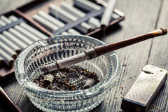 Glass ashtray with thin wooden pipes, cigarettes and lighter aro Royalty Free Stock Images