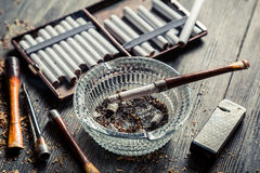 Glass ashtray with thin wooden pipes, cigarettes Stock Images