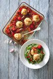 Oven baked meat balls with tomato sauce served with fresh zucchini salad. In glass baking dish there are oven baked meat balls with tomato sauce. Next baking Stock Photos