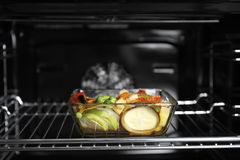 Glass baking dish with vegetables. In oven Royalty Free Stock Photography