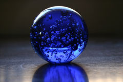 Glass Ball. One blue colored glass ball on a wooden table reflecting a portion of its color below. The ball has bubbles of air locked inside. Great for global Royalty Free Stock Image