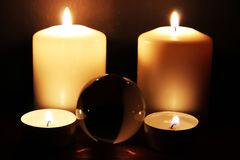 Glass ball and burning candles in the dark stock image