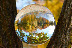 Glass ball. In a glass ball can you seen the landscape behind her stock photography