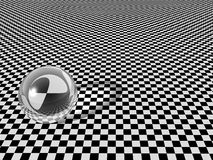 Glass ball on checkerboard royalty free stock photo