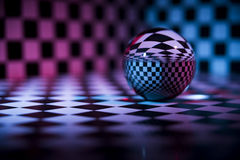 Glass ball. On a checkered background royalty free stock photo