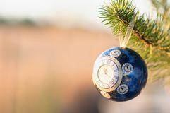 Glass ball, Christmas decoration with a clock on a Christmas tree, processing under a vintage photo, texture added, Royalty Free Stock Photo
