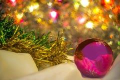 Glass ball with Christmas tinsel. Glass sphere with Christmas tinsel on the background star shaped lights Stock Photo