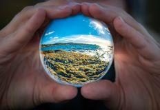Glass ball with coast of Sandefjord, Norway. Hands holding glass ball with view of coastline in Sandefjord, Norway royalty free stock photography