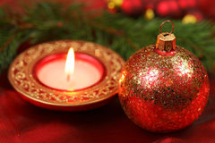Glass ball with gold stars. Glass ball and candle in red and gold colors. Decoration of Christmas table Royalty Free Stock Image