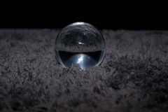 A glass ball on a hairy gray carpet in front of a black background. A dark scene with a oracle glass ball. Mysterious and esoteric royalty free stock photos