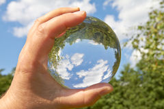 Glass ball. In a held glass ball can you seen the landscape behind her royalty free stock photo