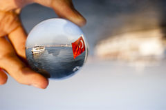 Glass ball. Izmir, Turkey - August 17, 2015: Glass ball, a ship and Turkish flag over the sea stock photos