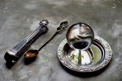 The glass ball lies on an old saucer.Old appliances. Grey concrete background. The glass ball lies on an old saucer. Old appliances. Grey concrete background Stock Image
