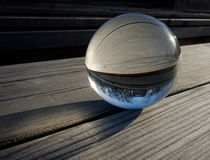 Glass ball refraction. Backgrounds and textures: glass ball on a wooden table, part of a landscape inside Stock Photos