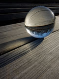 Glass ball refraction. Backgrounds and textures: glass ball on a wooden table, part of a landscape inside Royalty Free Stock Images