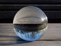 Glass ball refraction. Backgrounds and textures: glass ball on a wooden table, part of a landscape inside Royalty Free Stock Photos