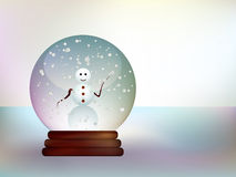 Glass ball with a snowman in a snowy landscape. Royalty Free Stock Photos